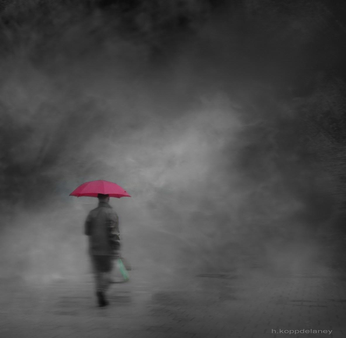 Éjsötét tömegben rózsaszín esernyő
